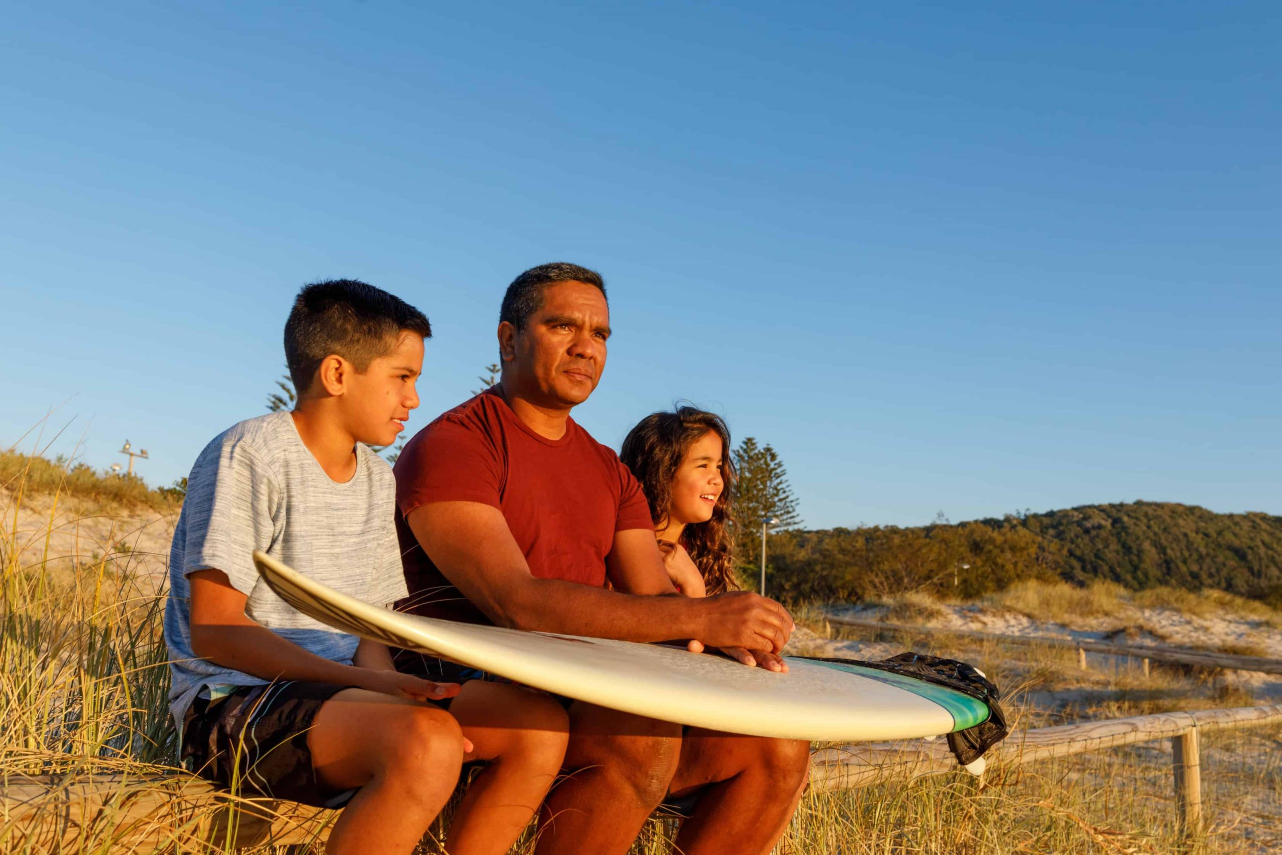 Father and children preparing to go for a surf